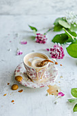 A cup of coffee decorated with milk a foam heart and flowers