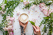 A cup of coffee with milk in sunlight, beside flowering branches