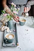Frau gießt Milchschaum in Kaffeetasse