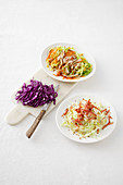 White cabbage salad with bacon and sesame, and a salad with roast chicken