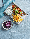 Kebab with french fries, sour cream and red cabbage