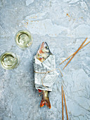 Wineglasses and raw fish wrapped in newspaper