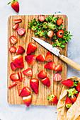 Strawberries on a wooden board, destemmed and sliced