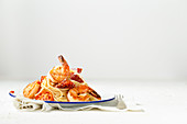 Spaghetti with pan seared prawns, oven roasted tomatoes and parmesan, on an enamel plate with a fork