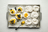 Meringue nests with lemon curd and blueberries on a baking tray