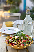 A vegetable salad and a bottle of water on a garden table