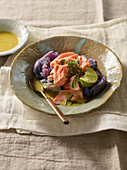 Salmon fillet on purple potatoes with a lime and Grana Padano vinaigrette