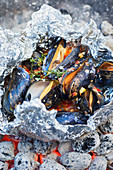 Grilled mussels in aluminium foil on glowing coals