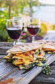 Panini with spinach and cheese served with red wine outside on a wooden surface