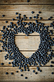 Blueberries arranged in a heart-shape on a wooden surface