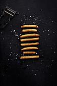 Pommes frites, aufgereiht auf schwarzem Untergrund