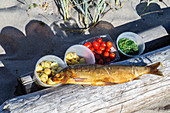 Smoked fish, potatoes, tomatoes and herbs on a wooden jetty on a beach