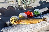 Geräucherter Fisch, Kartoffeln, Tomaten und Kräuter auf Holzsteg am Strand