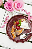 A slice of cherry pie with cream on a wooden table