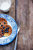 Pancakes with blueberries on a blue-and-white porcelain plate