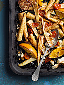 Oven-roasted vegetables with garlic and oranges on a baking tray