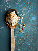 Butter with grated cheese and nuts on a wooden spoon