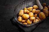 Potatoes in a wire basket being stored in a cool, airy place