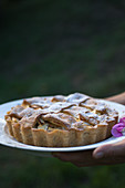 Woman serving ricotta tart with apples and sour cherries