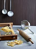Stilleben mit frischen Nudeln und Küchenutensilien