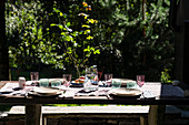 Covered garden table with colorful glasses and a water carafe