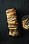 Olive pull-apart bread in a loaf tin and on a plate
