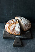 A loaf of country bread: classic sour dough bread, halved on a wooden board