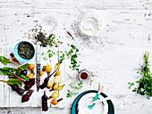 Stilleben mit Gemüse, Gewürzen, Kräutern und Tellern mit Besteck