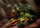 Carrot with lush green stem tomatoes pepper on round tray and cabbage in baskets on wooden table