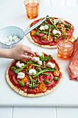 Regenbogen-Pizza mit Gemüse und Mozzarella belegen