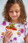 Mädchen isst ein Stück Gemüsepizza