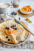 Fluffy omelette with blueberries and oranges served with coffee