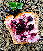 White bread with cream cheese and blackcurrants