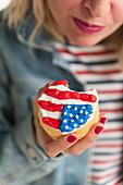 Frau hält Cupcake mit USA-Flagge