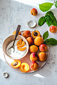 Sunny summer day, fresh apricots and yogurt in a bowl