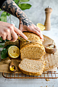 Person cuts a knife bread with lemon and Parmesan cheese