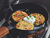 Corn fritters in a cast iron pan with sour cream and spring onions