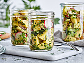 Potato salad with radishes and herbs in jars