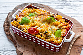 Pasta bake with cheese, tomatoes and basil