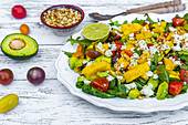 Fruity salad plate with arugula, tomatoes, mango, avocado, roasted pine nuts and feta