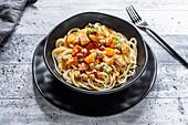 Spaghetti with pumpkin, salmon, chickpeas, guacamole and pomegranate seeds