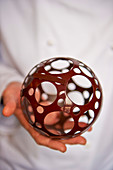A hand holding an openwork chocolate ball