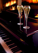 Two champagne glasses on a piano