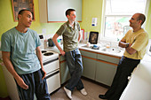 Teenagers in hostel kitchen with social worker