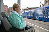 Woman wheelchair user waiting by a shelter at tram stop