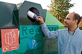 Man recycling a plastic bottle
