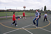 Group of teenage boys having a kick about with a football