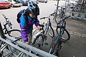 Woman locking up her bike in a works bike shed