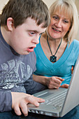 Mother and teenage son with Down Syndrome using a laptop