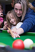 Adult teaching a child to play pool
